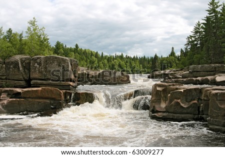 Rocky rapids in beautiful canadian river. This is Pabineau  river in the maritime province of New Brunswick. - stock photo