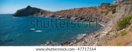 rocky sea bay with people bathing