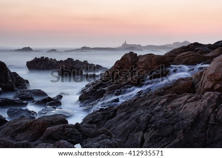 Rocky sea  beach from the north of Portugal at dusk seeing salt water cascade. Long exposure. - stock photo