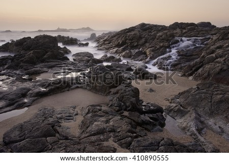 Rocky sea  beach from the north of Portugal at sunset seeing salt water cascade. Long exposure. - stock photo