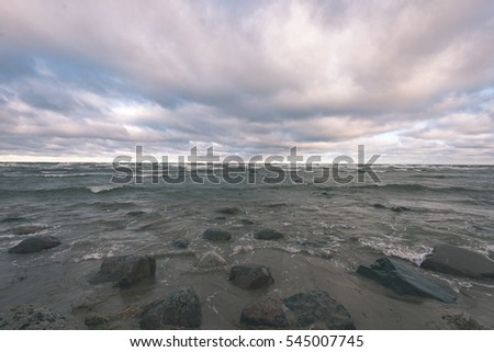 rocky sea beach with wide angle perspective over the sea clouds - vintage color film look