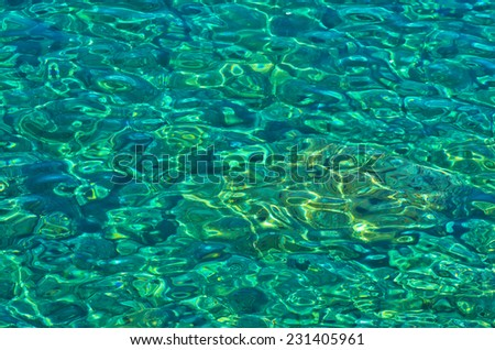Rocky sea floor visible thru crystal clear turqoise water of Aegean sea in Greece - stock photo