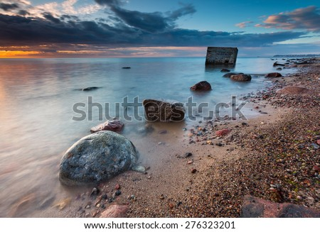 Rocky sea shore with world war II military bunker. Long exposure photo. Baltic sea shore. - stock photo