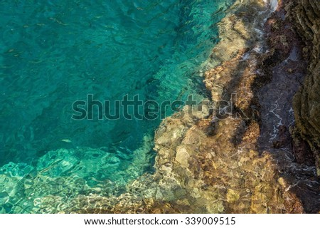 Rocky seabed under water. Gradient color from turquoise seawater to light brown rock. Photo was taken parallel to the horizon. - stock photo