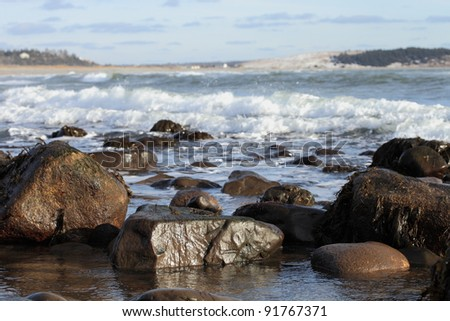 Rocky seashore and waves on a sunny winter's day - stock photo