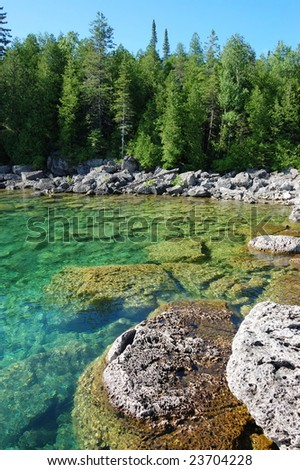 Rocky shore and clear lake water - stock photo