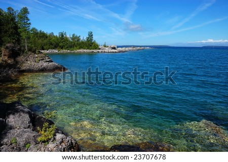 Rocky shore and clear lake water at Georgian Bay with blue sky