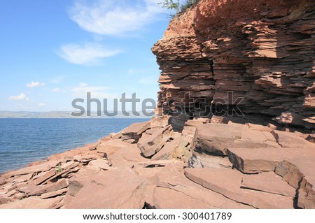 Rocky shore of Krasnoyarsk reservoir on the river Yenisei. Sunny day, blue sky, clear water, red stones on the shoreline. Siberian nature landscape, Russia. July 25, 2015. - stock photo