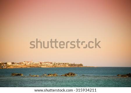Rocky shore of the Mediterranean Sea. Town on the horizon. Toned. - stock photo
