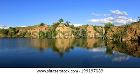 Rocky shore on blue lake, wide view  - stock photo