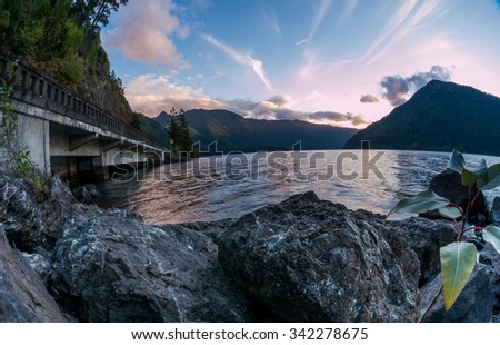 Rocky shore with bright blue water and mountains behind.  Taken at Lake Crescent, in Olympic National Park, Washington - stock photo