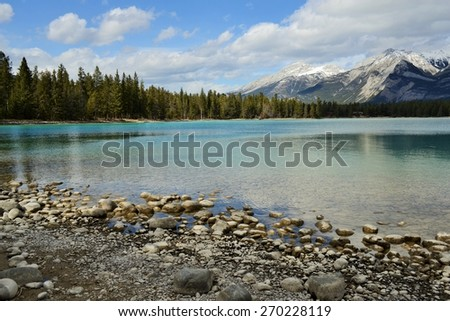Rocky Shoreline of Lake Edith, Crystal Clear Water with Mountains and Evergreen Forest in Background - stock photo