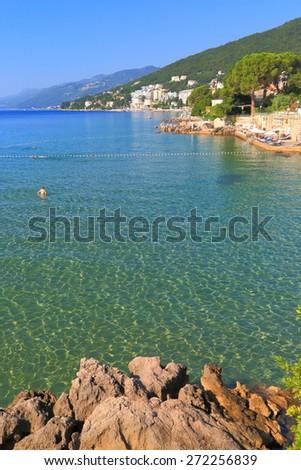 Rocky shores of the Adriatic sea near traditional resort, Opatija, Croatia - stock photo