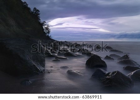 Rocky shores of the Baltic Sea at night with long exposure - stock photo