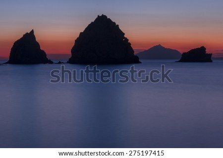 Rocky silhouettes after the sunset, in the greek island of Lemnos. - stock photo