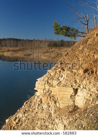 Rocky, steep bank of a mountain lake - stock photo