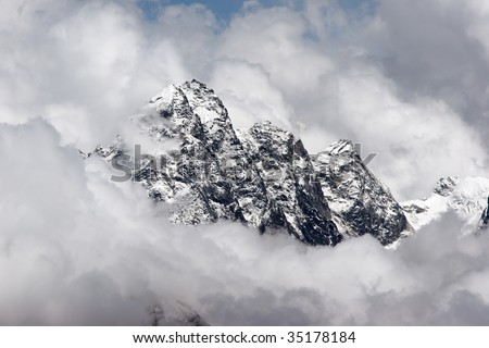 Rocky summit sticking out of clouds, Himalaya - stock photo