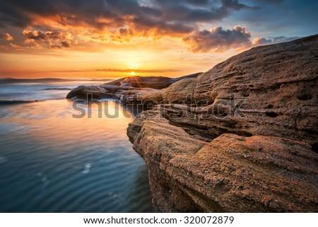 Rocky sunrise. Sea sunrise at the Black Sea coast near Ravda, Bulgaria - stock photo