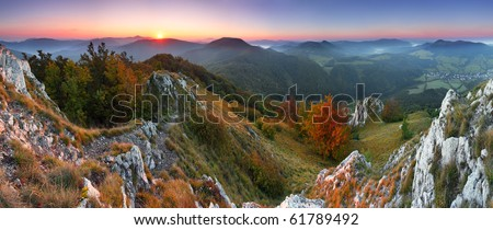 Rocky towny in green mountain at sunrise - stock photo