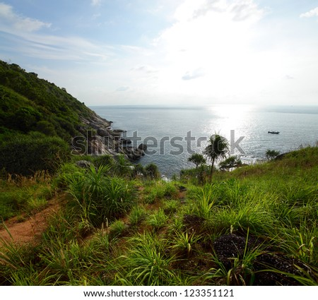 Rocky wild coast of Andaman sea with green lush meadows and steep cliffs
