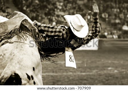 Rodeo bull rider (in soft focus and vintage/sepia tone) trying to stay on a twistng bull. - stock photo