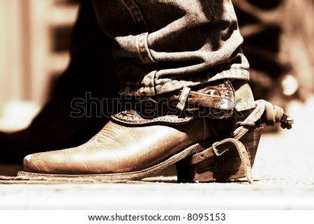 Rodeo Cowboy Boot and Spur in sunlight and shadow with high contrast copper tone (shallow focus). - stock photo
