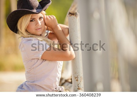Rodeo, cowboy, western. Young, happy and sexy cowgirl in western style. Young sexy Woman wearing cowboy hat. outdoor fashion portrait cowgirl in hat in the western village - stock photo