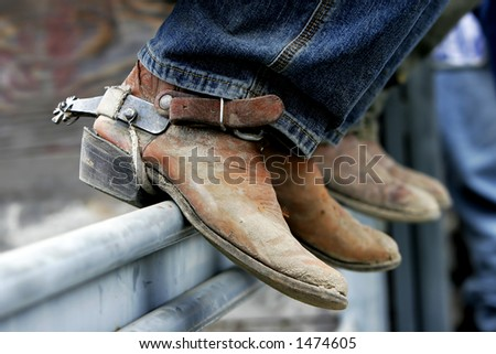 Rodeo cowboys' experienced boots & spurs on an iron rail (shallow focus) - stock photo