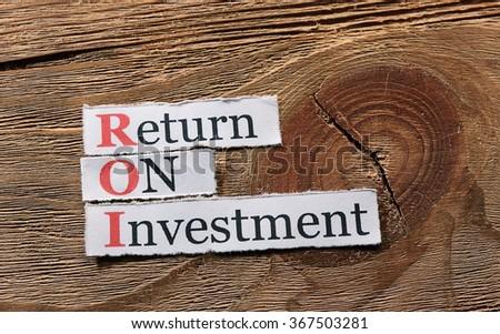 ROI acronym  Return On Investment on paper on wood - stock photo