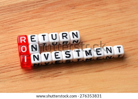 ROI Return On Investment written on dices on wooden  background - stock photo