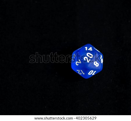 Role playing die showing a natural 20 roll on a d20 form a set of dice - set to the side for easy addition of wording - stock photo