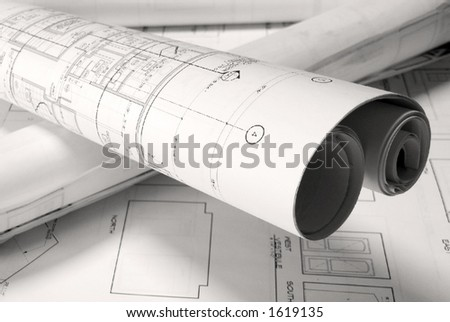 roled -up plans on the table - stock photo