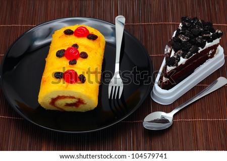 Roll cake and orange marmalade cake, cookie, milk. - stock photo