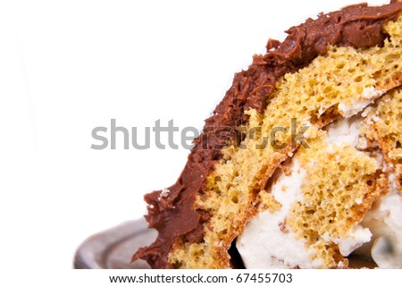 roll cake with chocolate icing and whipped cream filling depth of field - stock photo