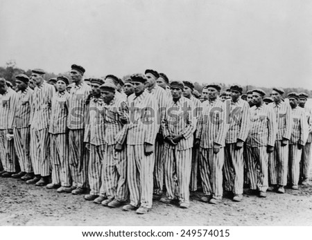 Roll call at Buchenwald concentration camp, ca.1938-1941. Two prisoners in the foreground are supporting a comrade, as fainting was frequently an excuse for the guards to 'liquidate' useless inmates. - stock photo