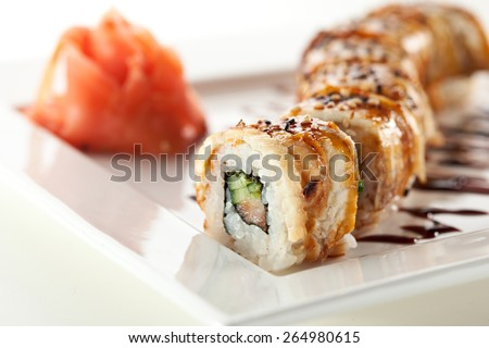 Roll made of Fresh Salmon, Smoked Eel, Cream Cheese and Cucumber inside. Topped with Smoked Eel - stock photo