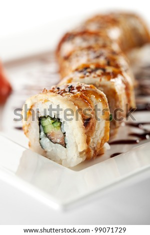 Roll made of Fresh Salmon, Smoked Eel, Cream Cheese and Cucumber inside. Topped with Smoked Eel (unagi) - stock photo