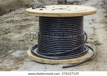 Roll of black industrial underground cable on large wooden reel at construction site. Four core al cable. Selective focus and shallow dof. - stock photo