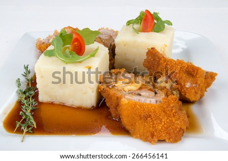 Roll of chicken, mashed potatoes, gravy, tomato and spices. - stock photo