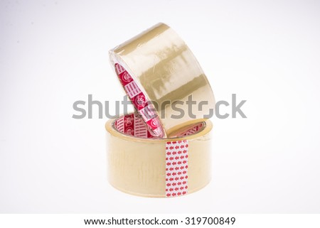 Roll of clear transparent sticky tape isolated on white - stock photo