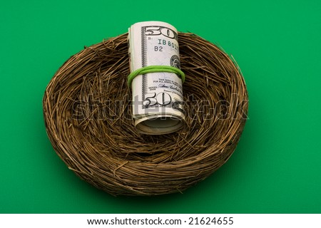 Roll of fifty dollar bills sitting in nest on green background, nest egg