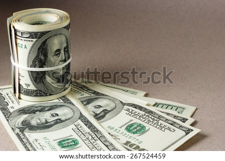 Roll of hundred-dollar bills bounded by rubber band. Vintage dollar background