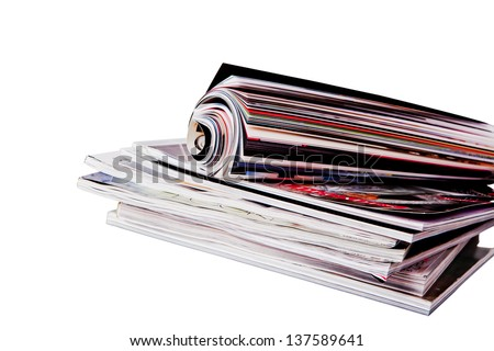 roll of magazine on a stock of magazines isolated on white background