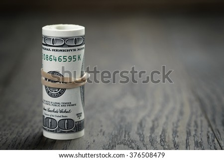 roll of new style hundred dollar bills on table - stock photo
