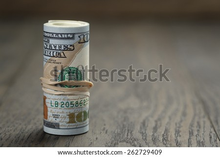 roll of new style hundred dollar bills stand on wooden table - stock photo