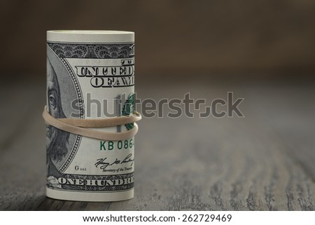 roll of old style hundred dollar bills stand on wooden table - stock photo