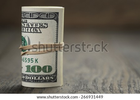 roll of old style hundred dollar bills stand on wooden table, Shallow DOF - stock photo