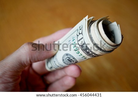 Roll of paper banknotes (American Dollars, USD) hold by a male hand as a symbol of ongoing money transfer (payment, bribery or gift)  - stock photo