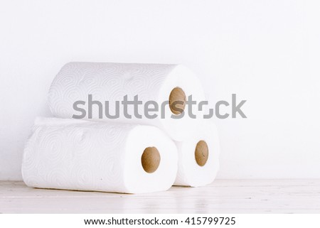 Roll of paper towel on wooden table - stock photo