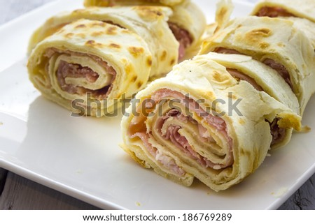Roll of piadina with ham and cheese - stock photo